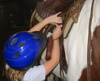 Young student, learning to girth a lesson horse at Jack Tone Ranch.